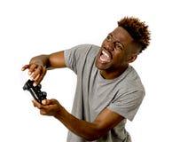 Afro- amerikansk man som använder den avlägsna kontrollanten som spelar den upphetsad videospelet som är lycklig och Arkivfoto
