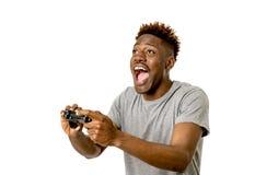 Afro- amerikansk man som använder den avlägsna kontrollanten som spelar den upphetsad videospelet som är lycklig och Royaltyfri Fotografi