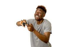 Afro- amerikansk man som använder den avlägsna kontrollanten som spelar den upphetsad videospelet som är lycklig och Royaltyfri Bild