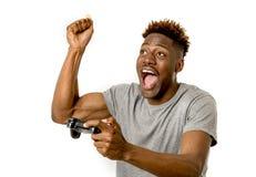 Afro- amerikansk man som använder den avlägsna kontrollanten som spelar den upphetsad videospelet som är lycklig och Arkivbild