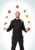 Afro- amerikansk yrkesmässig kock som jonglerar grönsaker Arkivfoton