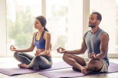 Afro- amerikanska par som gör yoga Arkivfoton