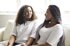 Afro amerikanskt sammanträde för tillgivna vänner på soffan royaltyfri fotografi