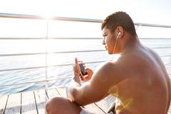 Afro amerykańscy sporty obsługują odpoczywać po treningu i słuchają muzykę Zdjęcie Stock