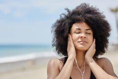 Afro amerykańska kobieta relaksuje na plażowej słuchającej muzyce Zdjęcia Royalty Free