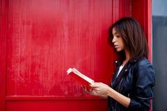 Afro amerykańska kobieta stojąca outdoors czyta literaturę podczas gdy Obrazy Royalty Free