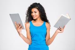 Afro amerykańska kobieta wybiera między pastylka komputerem lub papierową książką Obrazy Stock