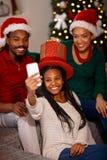 Afro Amerykańska rodzina w Santa kapeluszach bierze selfie na bożych narodzeniach Fotografia Stock