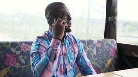 Afro amerykański mężczyzna czeka jego rozkaz dzwoni smartphone obsiadanie w kawiarni i opowiada zdjęcie wideo