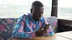 Afro amerykański mężczyzna czeka jego rozkaz wyszukuje smartphone obsiadanie w kawiarni zbiory
