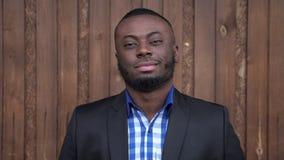 Afro amerykański mężczyzna w kostiumu uśmiechniętym i patrzeje kamerę na ciemnym drewnianym tle zdjęcie wideo