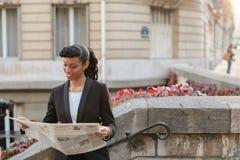 Afro Amerykańskiej dziewczyny czytelnicza gazeta z zakończeniem up twarz Zdjęcia Royalty Free
