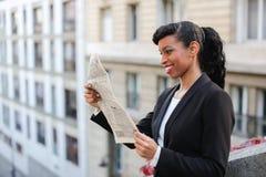 Afro Amerykańskiej dziewczyny czytelnicza gazeta z zakończeniem up twarz fotografia royalty free