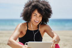 Afro amerykańskiej kobiety słuchająca muzyka na pastylce na plażowy śmiać się Obrazy Stock