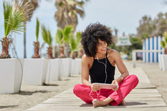 Afro amerykańskiej kobiety słuchająca muzyka na pastylce na zewnątrz śmiać się Zdjęcia Stock