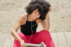Afro amerykańskiej kobiety słuchająca muzyka na pastylki ono uśmiecha się Zdjęcie Royalty Free