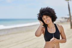 Afro amerykańskiej kobiety słuchająca muzyka na wiszącej ozdobie uważnie Zdjęcia Royalty Free