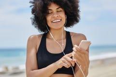Afro amerykańskiej kobiety słuchający audiobook na mobilny ono uśmiecha się Zdjęcie Royalty Free