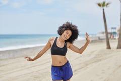 Afro amerykańskiej kobiety słuchający muzyczny taniec na plaży szczęśliwie Zdjęcia Stock