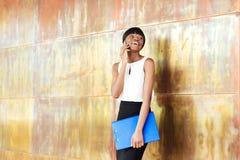 Afro amerykańska kobieta opowiada na telefonie w biurze Zdjęcia Royalty Free