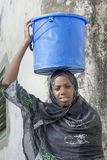 Afro beauty carrying a bucket of water in a slug Stock Photography