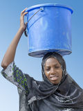 Afro beauty carrying a bucket of water  Royalty Free Stock Photos