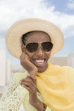 Afro beauty wearing a boater straw hat and a pair of dark sunglasses Royalty Free Stock Image