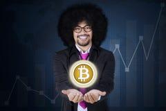 Afro biznesmen pokazuje bitcoin na jego ręki Obrazy Royalty Free