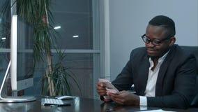 Afro biznesmena liczenia gotówka, siedzi przy biurkiem w biurze Obrazy Royalty Free