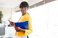 Afro bizneswomanu mienia amerykańska falcówka i smartphone Fotografia Royalty Free