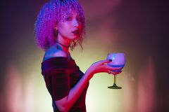 Afro black woman holding an alcoholic blue mystery drink with sp. Sexy afro black woman holding an alcoholic blue mystery drink with spooky background Royalty Free Stock Image