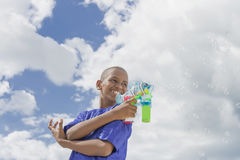 Afro boy playing with a bubble gun under the sun Stock Images