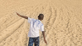Afro boy walking in the sand, ten years old Stock Images