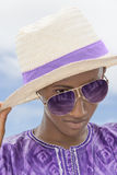 Afro boy wearing a boater straw hat and a pair of sunglasses Stock Photos