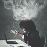 Afro businessman angry with his broken laptop. Afro businessman looks mad while shouting at his broken laptop and sitting with smoke over his head royalty free stock photos
