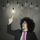 Afro businessman chooses light bulb Royalty Free Stock Images