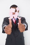 Afro businessman covered in blank notes gesturing thumbs up Stock Photos