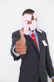 Afro businessman covered in blank notes gesturing thumbs up Stock Images