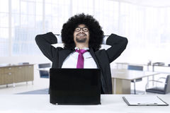 Afro businessman daydreaming in office. Young Afro businessman with curly hair, sitting in the office while daydreaming with laptop on the table Royalty Free Stock Photo