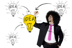 Afro businessman drawing bright light bulb Royalty Free Stock Photography