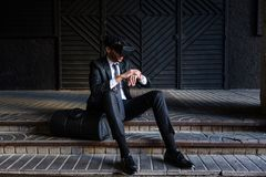 Afro businessman playing virtual reality simulation. Afro businessman dressing a suit, sitting and playing virtual reality simulation Royalty Free Stock Images