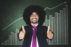 Afro businessman with financial graph. Image of cheerful Afro businessman showing thumbs up while standing with a financial graph on the chalkboard Royalty Free Stock Photography