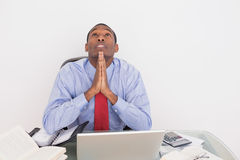 Afro businessman looking up with joined hands at desk Stock Photo