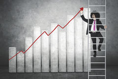 Afro businessman makes chart on the ladder Stock Photos