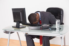 Afro businessman resting head on keyboard in office Stock Image