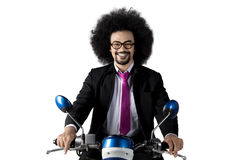 Afro businessman riding motorcycle in studio Royalty Free Stock Photography