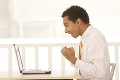 Afro businessman screamin in joy in front of his notebook Royalty Free Stock Image