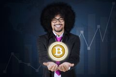 Afro businessman showing bitcoin on his hands royalty free stock images