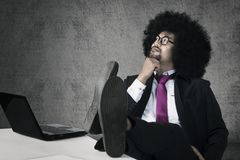 Afro businessman thinking an idea. Afro businessman is thinking an idea while sitting with laptop and his foot on the table royalty free stock photos