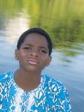 Afro chłopiec pozycja blisko wody, dziesięć lat Fotografia Royalty Free